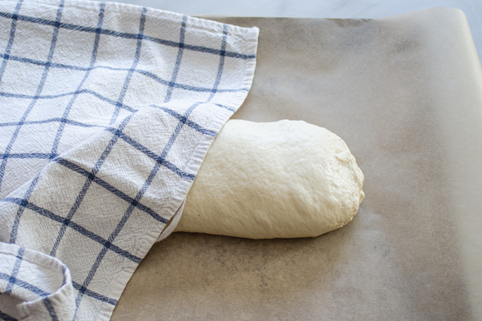 The formed loaf on a parchment lined baking sheet with a tea towel partially covering it.