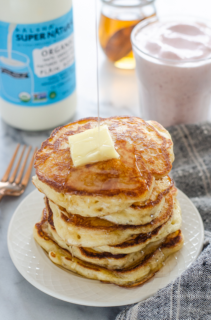 Drizzling maple syrup onto a stack of sourdough pancakes.