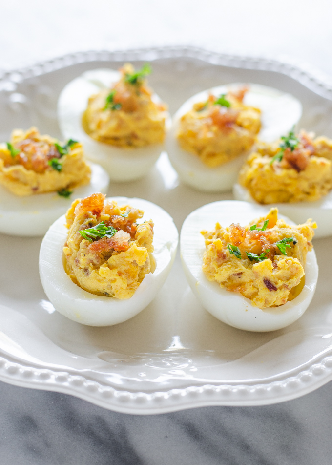 Deviled eggs with bacon and garnished with parsley on a pretty plate.
