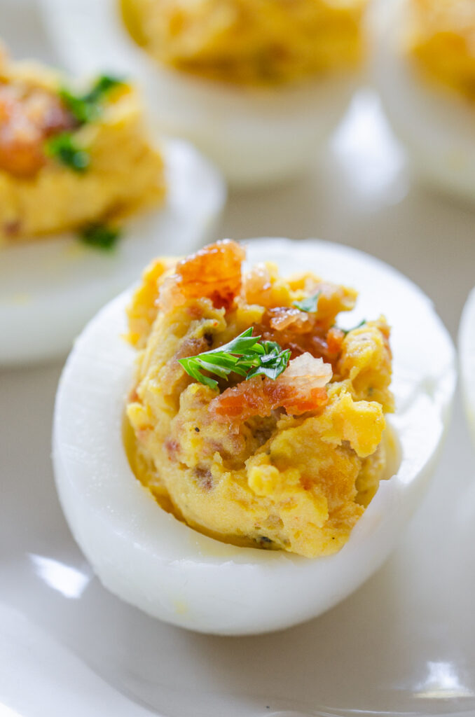 A close up shot of deviled eggs with bacon garnished with parsley.
