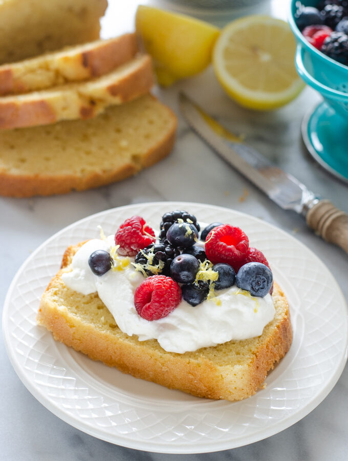 A slice of sour cream pound cake loaf topped with whipped cream and berries.