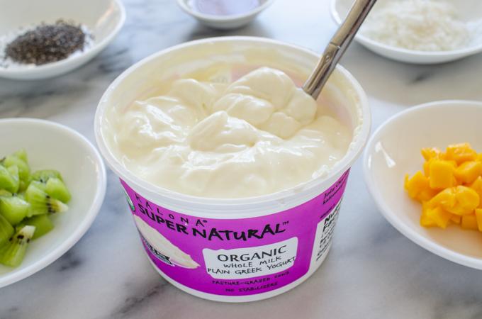 Kalona SuperNatural Greek yogurt on a marble surface with ingredients around it.