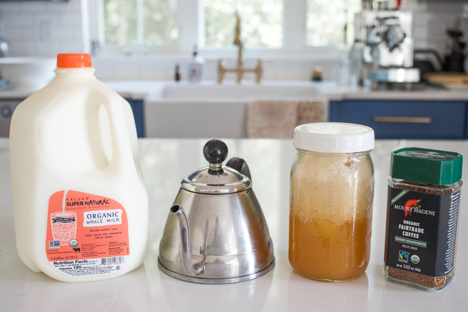 Milk, a tea kettle, honey, and instant coffee on a countertop.