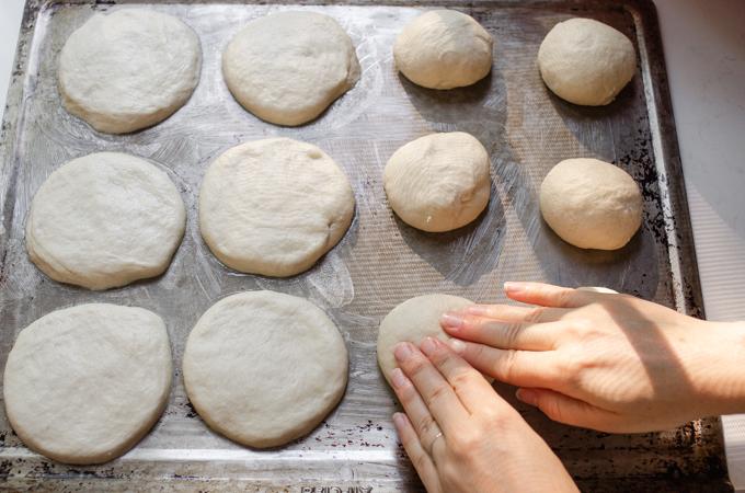 Flattening the dough ball on a cookie sheet.