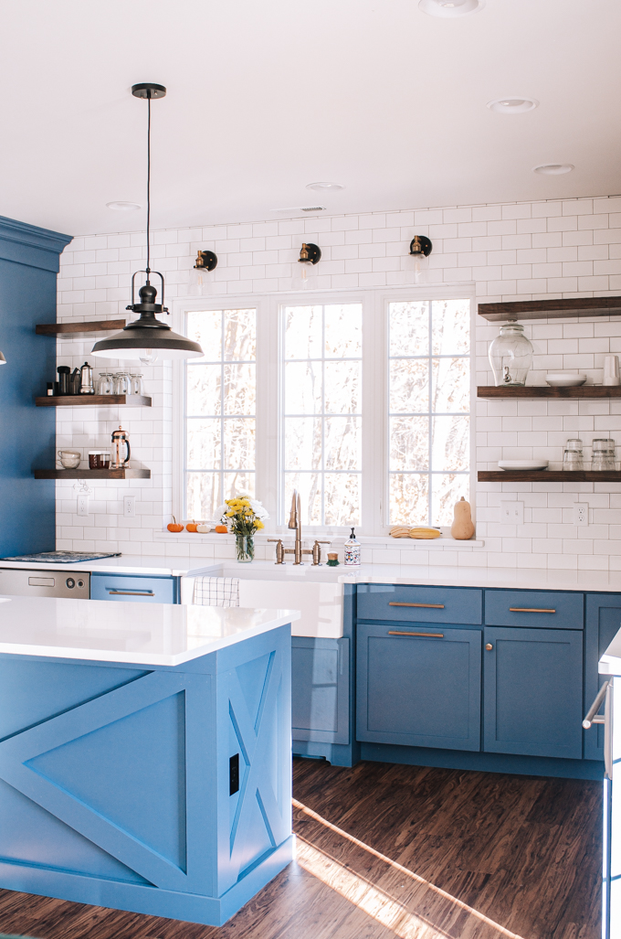 Transitional industrial farmhouse style kitchen with blue cabinets, subway tile backsplash, white quartz counters, and open shelving.