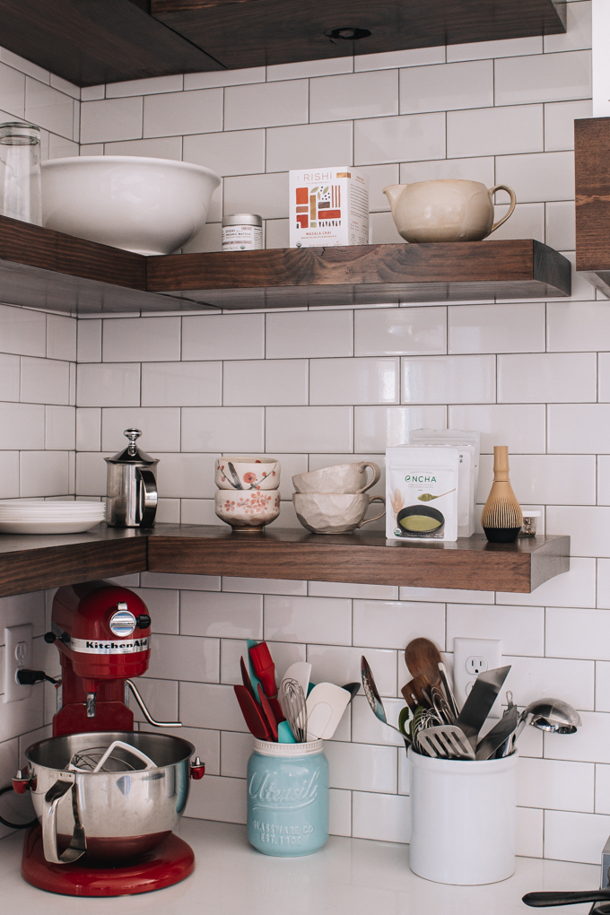 Open shelving with subway tile backsplash up to the ceiling.