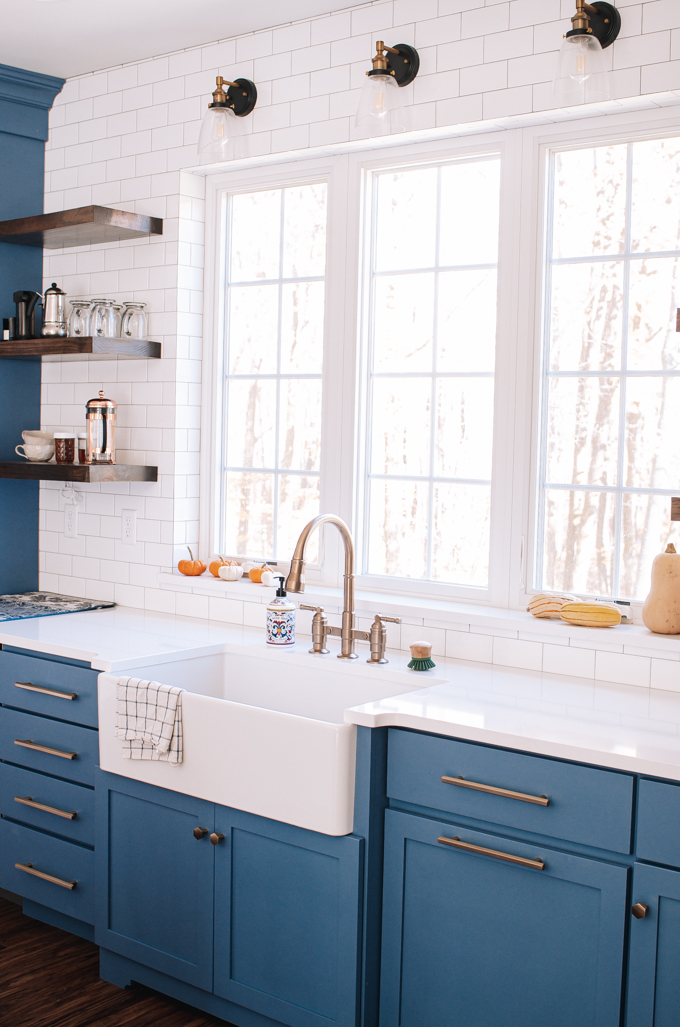 Blue transitional cabinets with white quartz countertops and a white apron front kitchen sink in front of window.