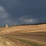 Dark clouds over farmland.