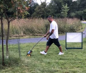 man using magnet to clean the yard