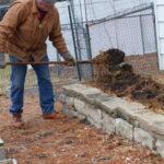 Man using garden fork to turn soil