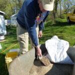 man mixing seed in wheelbarrow