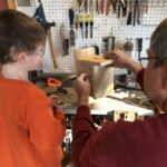 man and boy make birdhouse