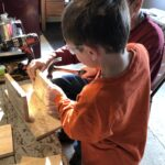 Boy and man make bird house