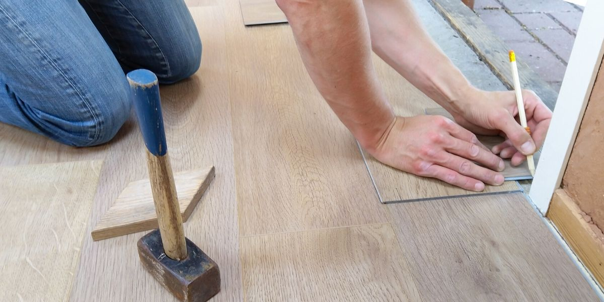 A man installing a floating floor in his house.