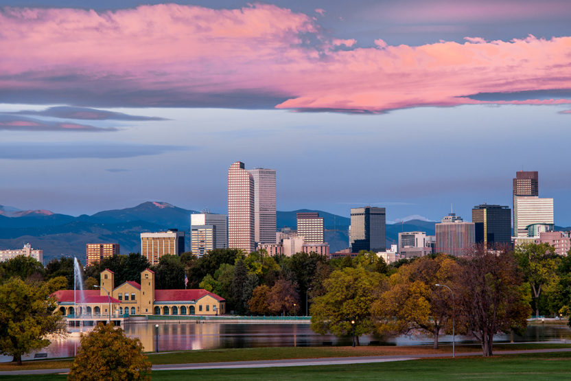 The Denver downtown skyline is seen looking west from Denver City Park at sunrise, with pleasing light and pink clouds above the Rocky Mountains in the background.