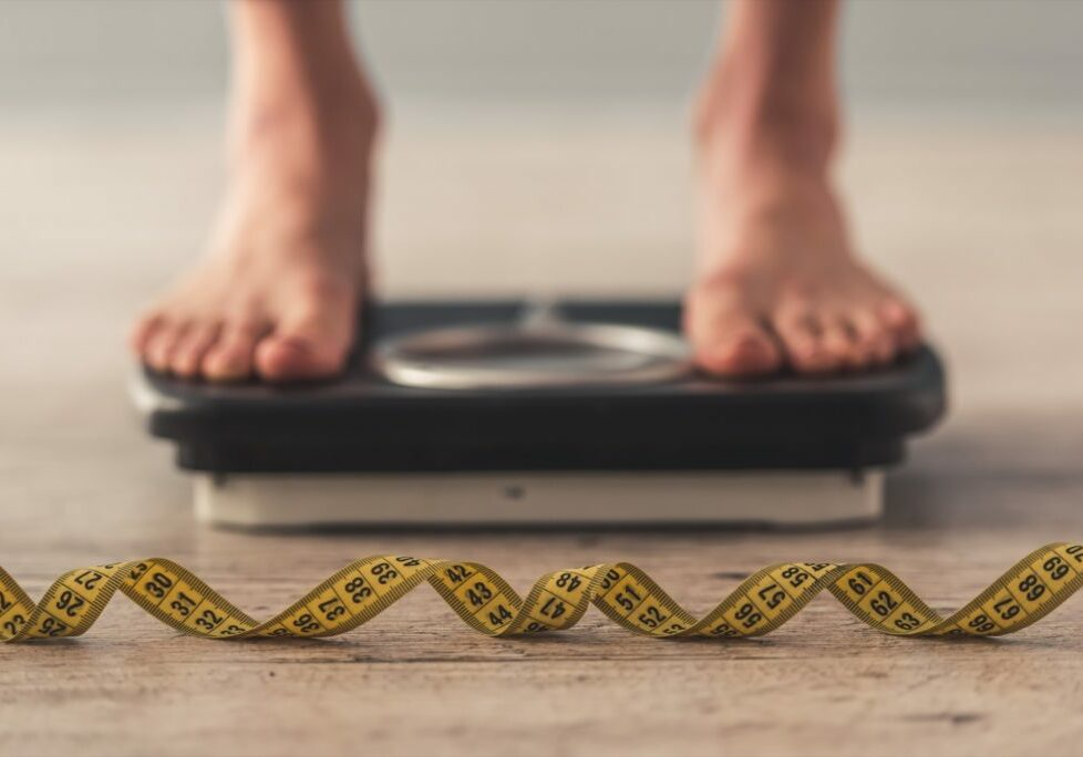 Cropped image of woman feet standing on weigh scales, on gray background. A tape measure in the foreground