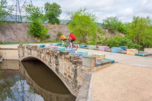 Bicyclists on Mission Reach bridge near Concepcion Park