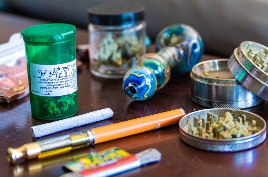 Vape pen, smoking pipe, lighter, grinder and marijuana buds on a table