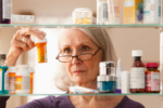 Woman looking at medications in medicine cabinet