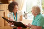 A care worker makes a house call to a senior client at her home