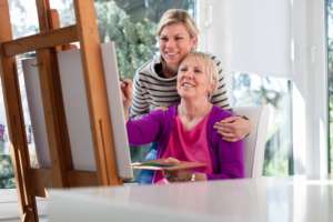 Caregiver supporting client as she paints a picture