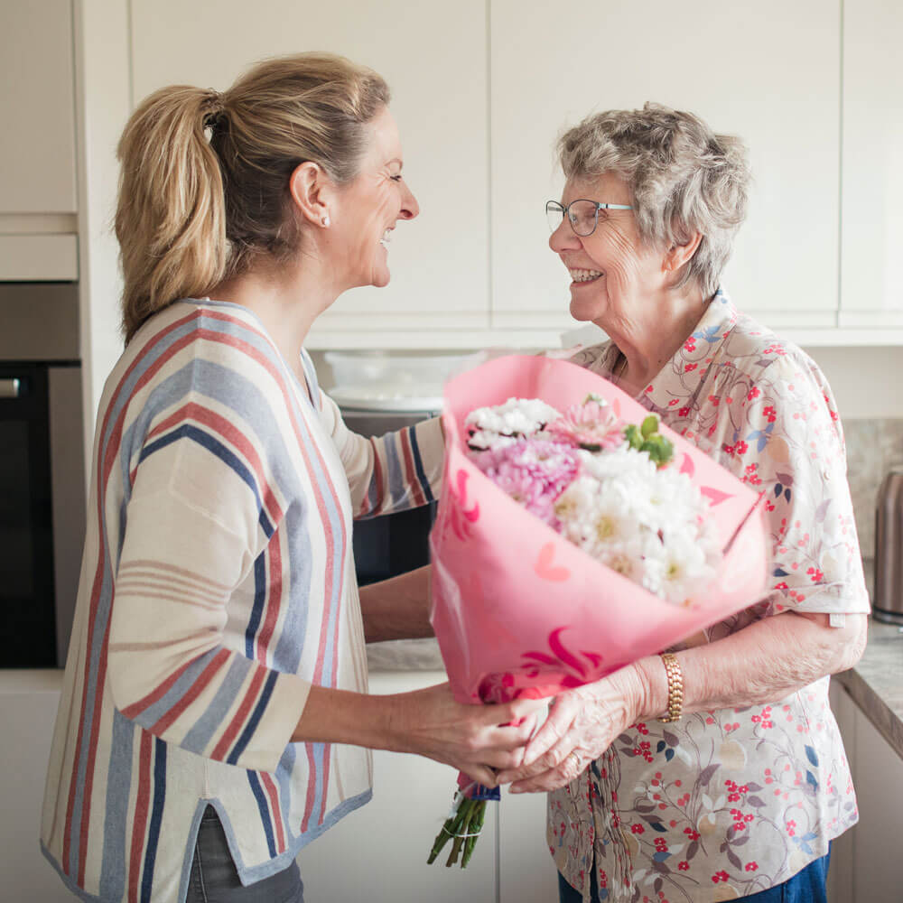 Daughter or caregiver standing in kitchen, handing a senior woman flowers