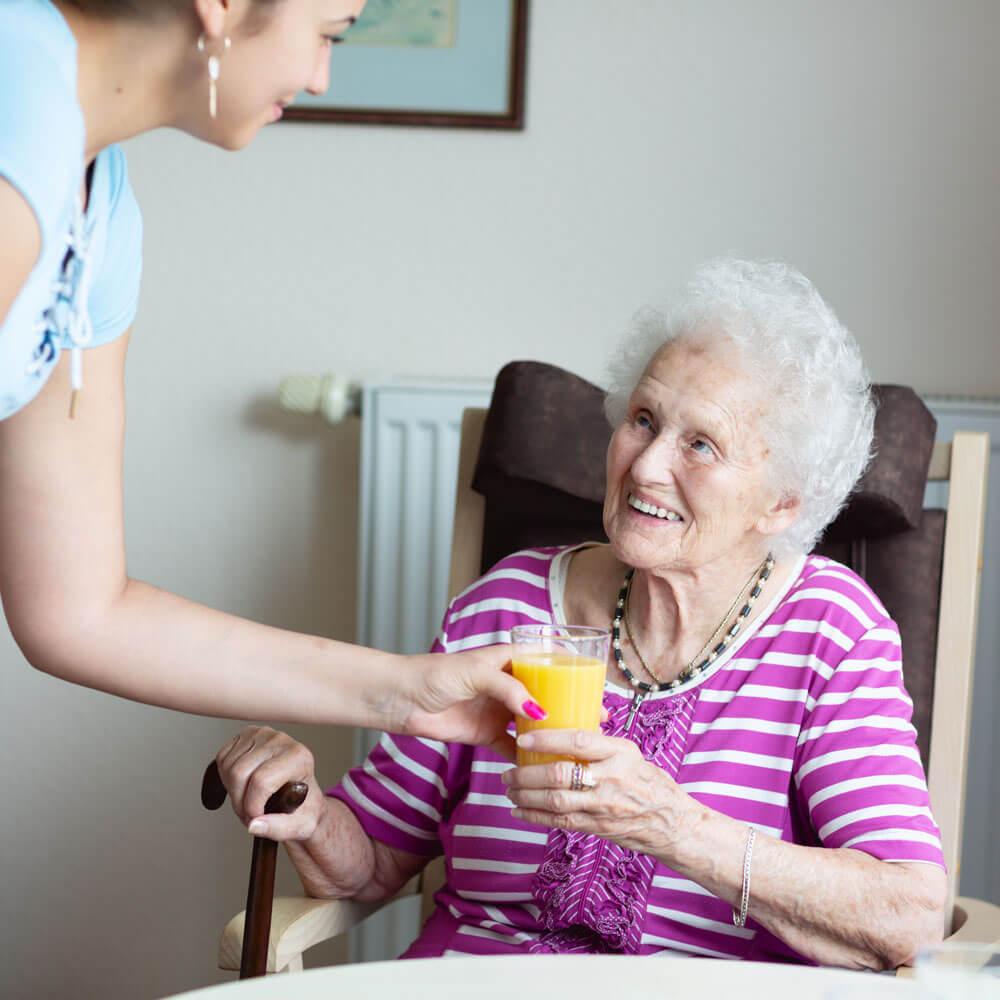 Caregiver handing senior woman a glass of orange juice