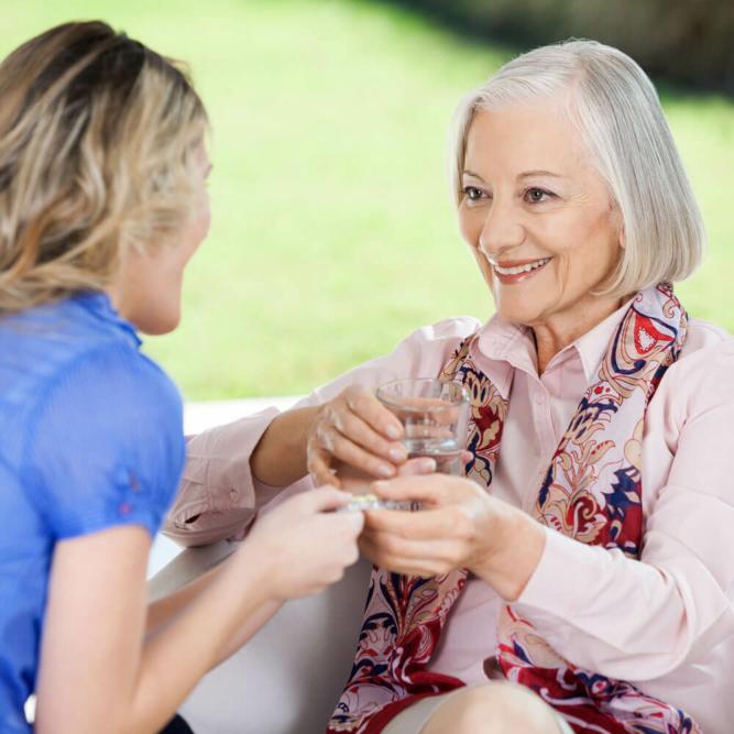 Caregiver handing a patient medication