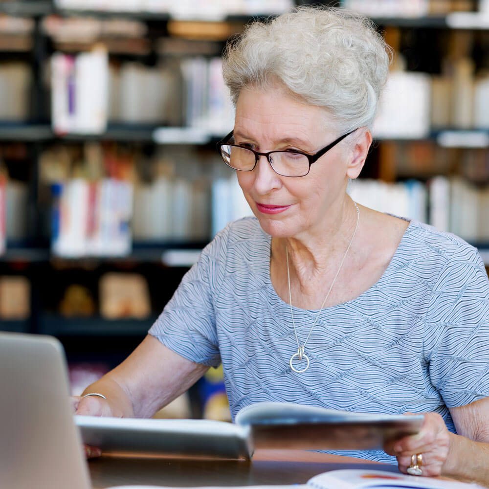 Older woman doing research in a library and online