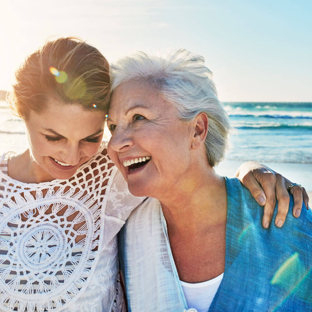 Mother and daughter walking on the beach, smiling and laughing