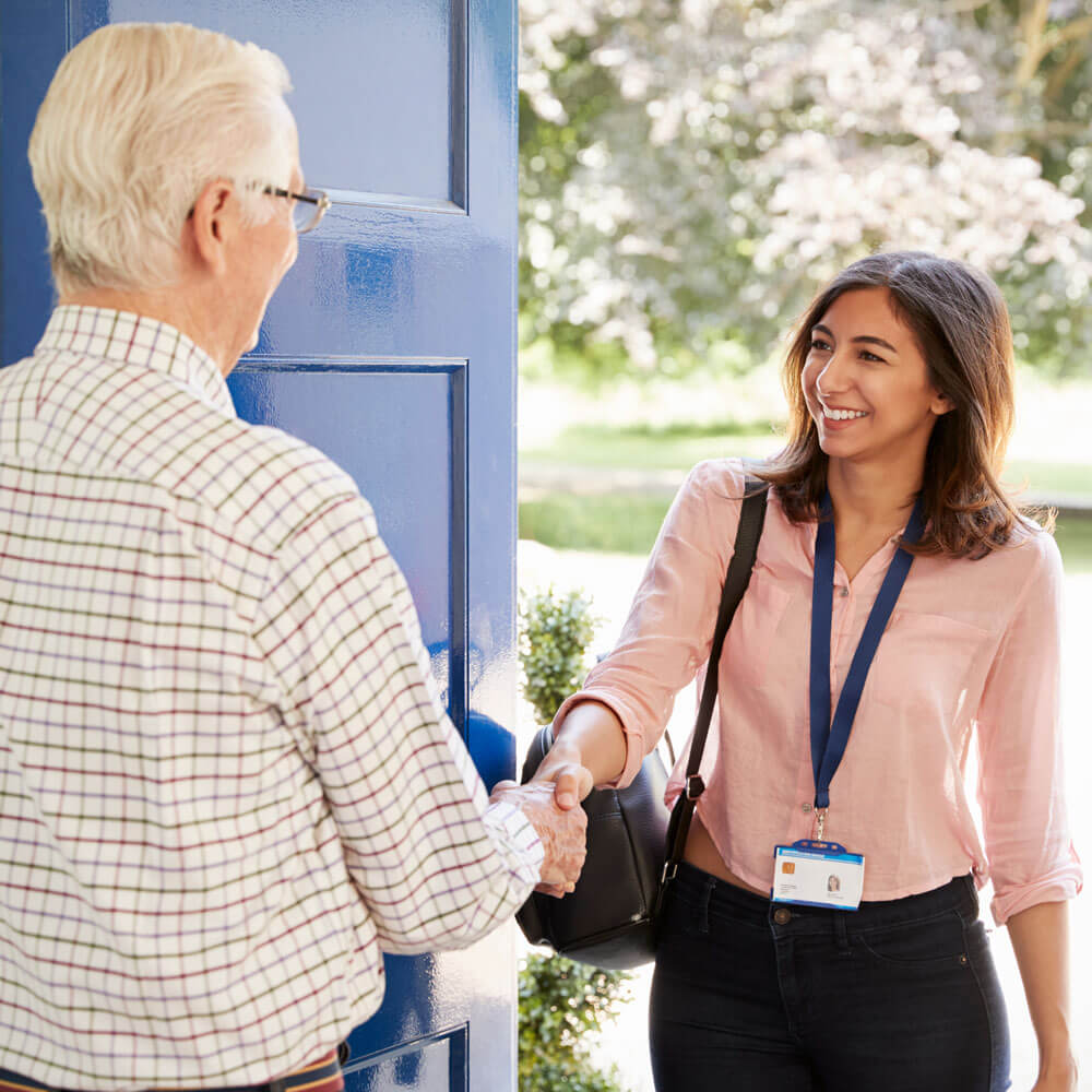 Caregiver being greeted at the door by senior client