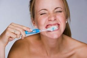 mujer lavandose los dientes con fuerza