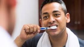 hombre cansado cepillandose los dientes