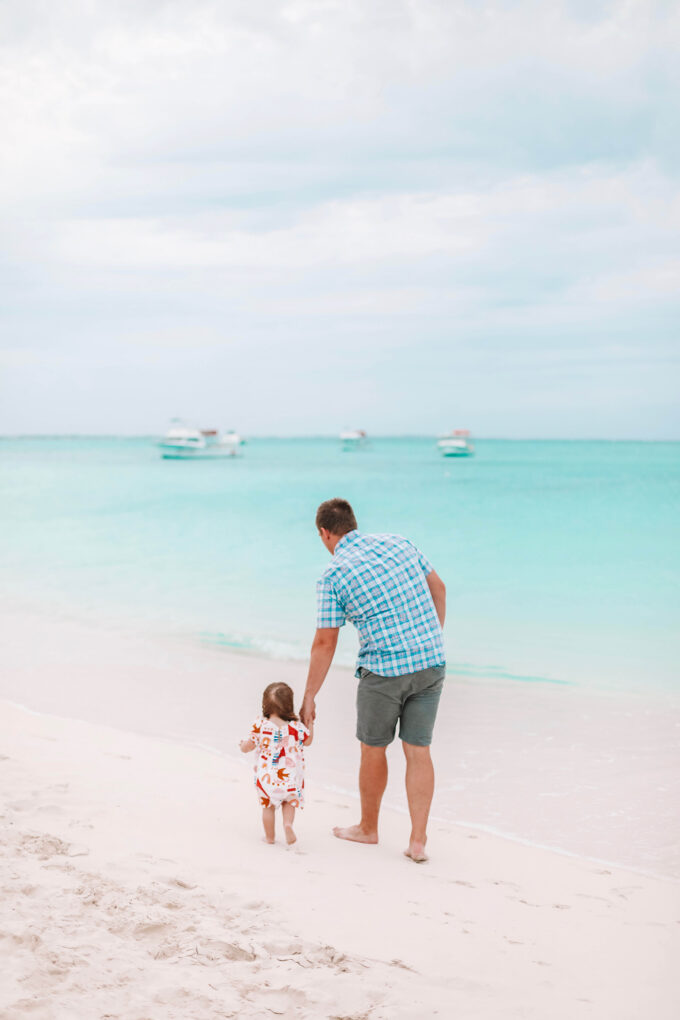daddy and daughter walking on beach