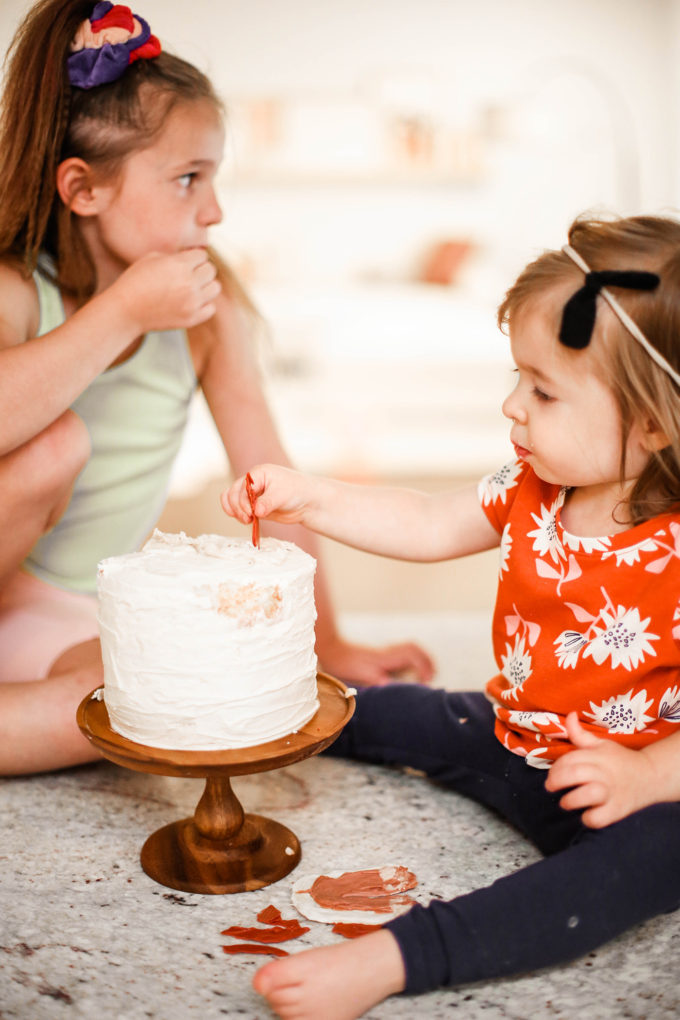 little girls playing with birthday cake