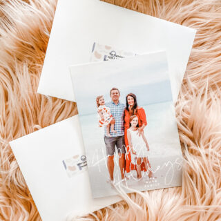 holiday cards and envelopes styled on pink fur blanket