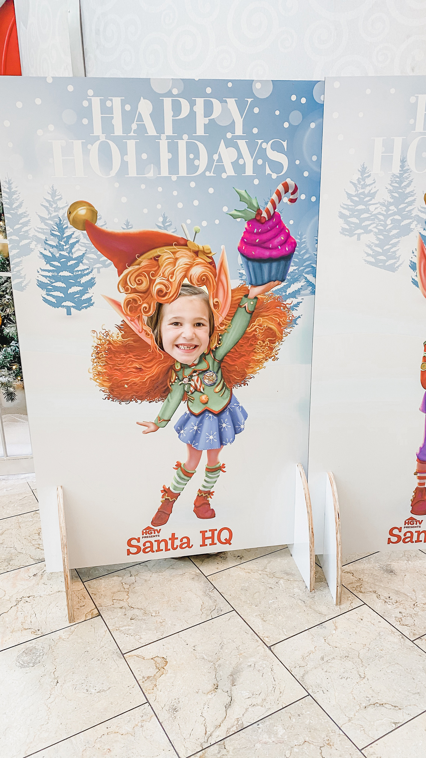 Little girl posting in head cutout of elf body