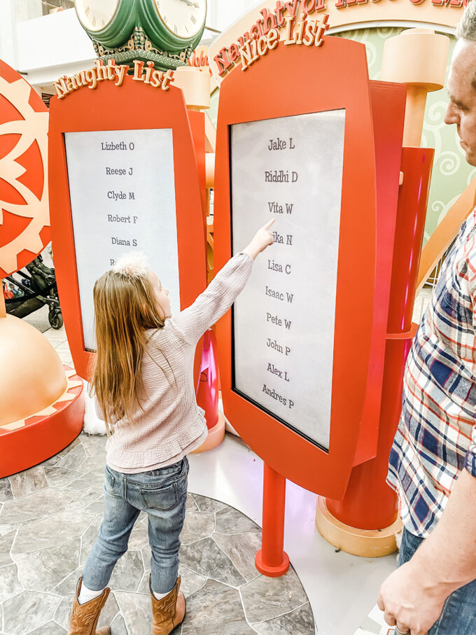 """little girl pointing to her name being on Santa's """"NICE"""" list"""