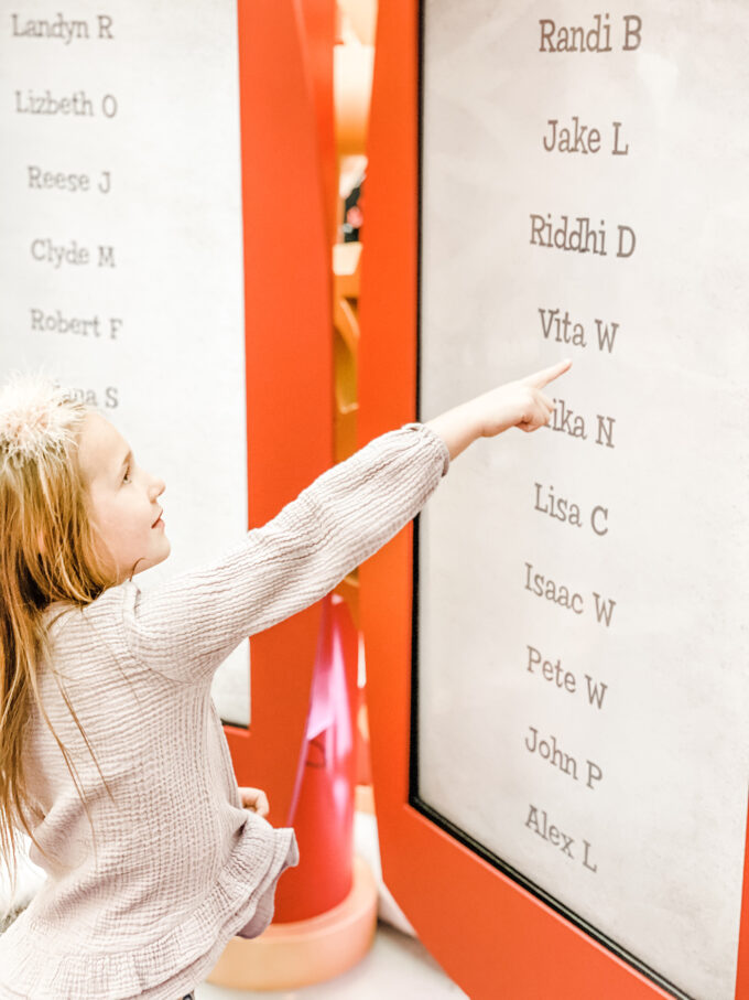 """little girl pointing to her name on Santa's """"nice"""" list"""