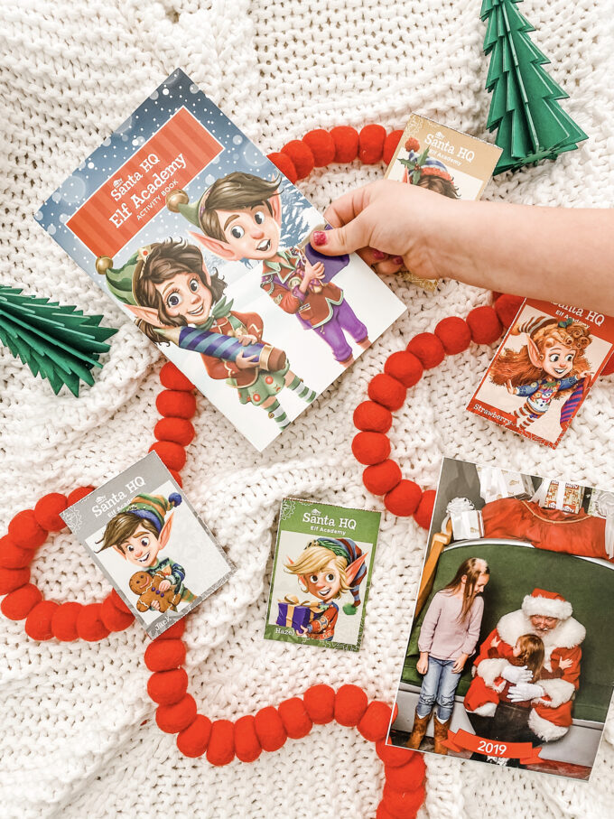 little girl reaching for elf academy activity book with other activities scattered with christmas items