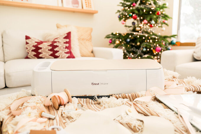 cricut maker and tools styled in front of christmas tree