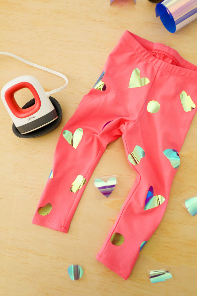 pink valentine's day leggings in flat lay setup with holographic shapes ironed on