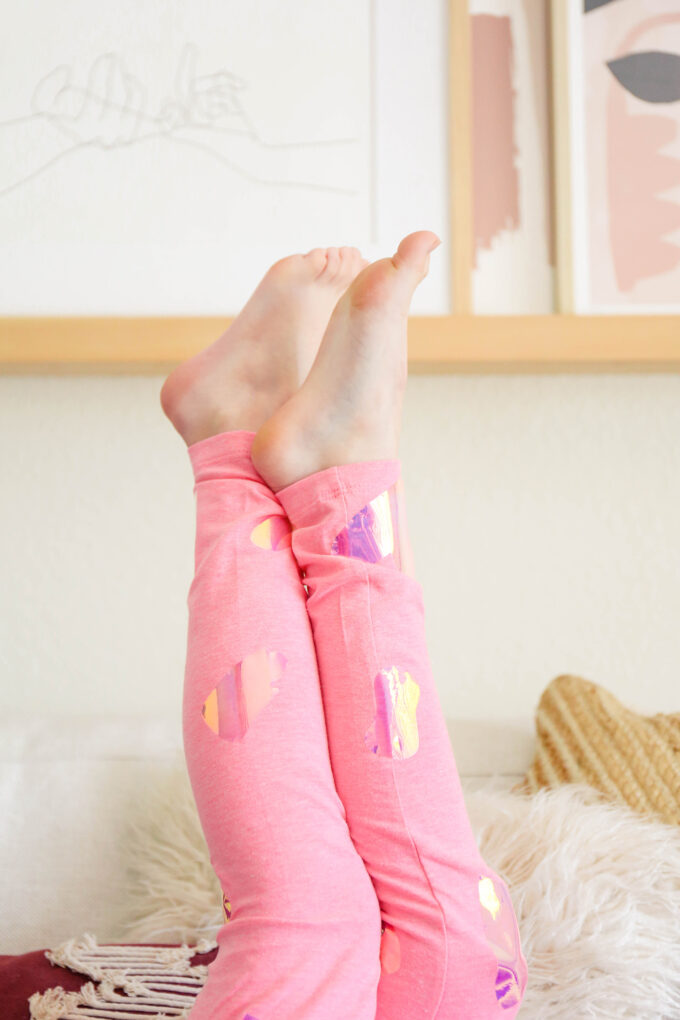 little girl's legs in the air with pink valentine's day leggings