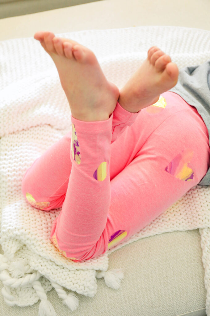 little girl crossing legs with pink valentine's day leggings