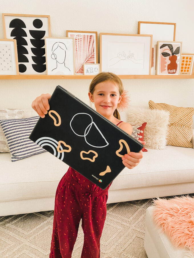 little girl holding chromebook with personalized stickers