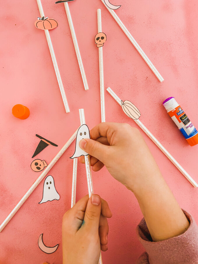 little girl hands glueing halloween printables to straws
