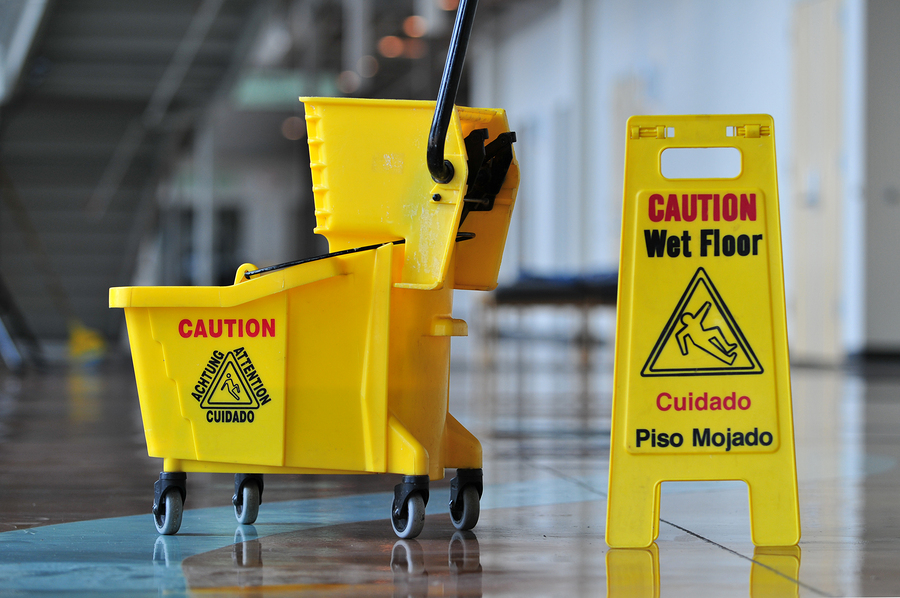 Mop bucket and caution sign inside a building