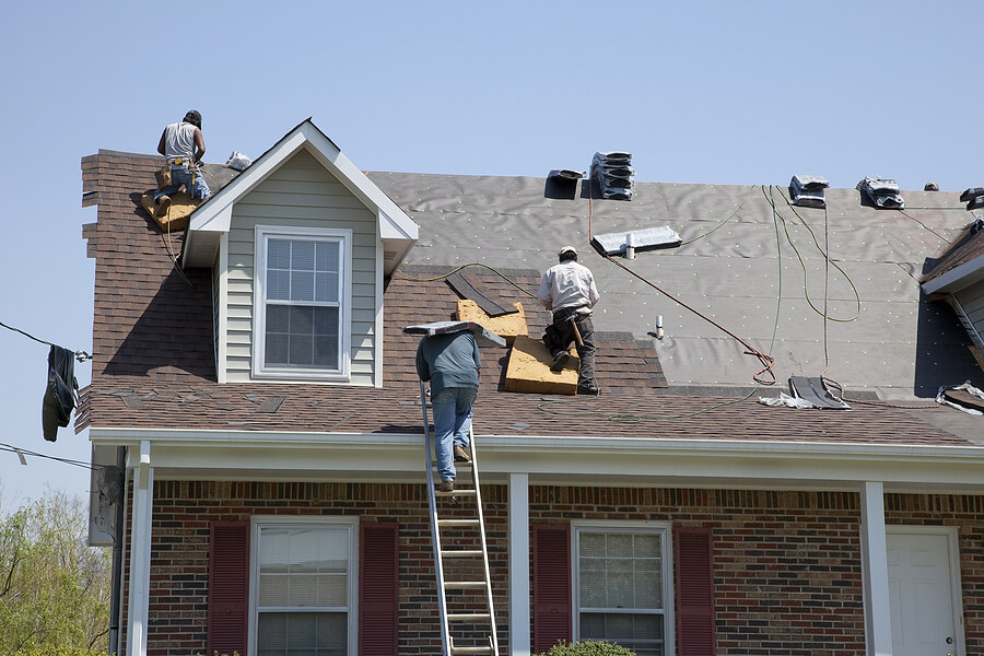 Roofers roofing after settlement with help from an insurance claim lawyer