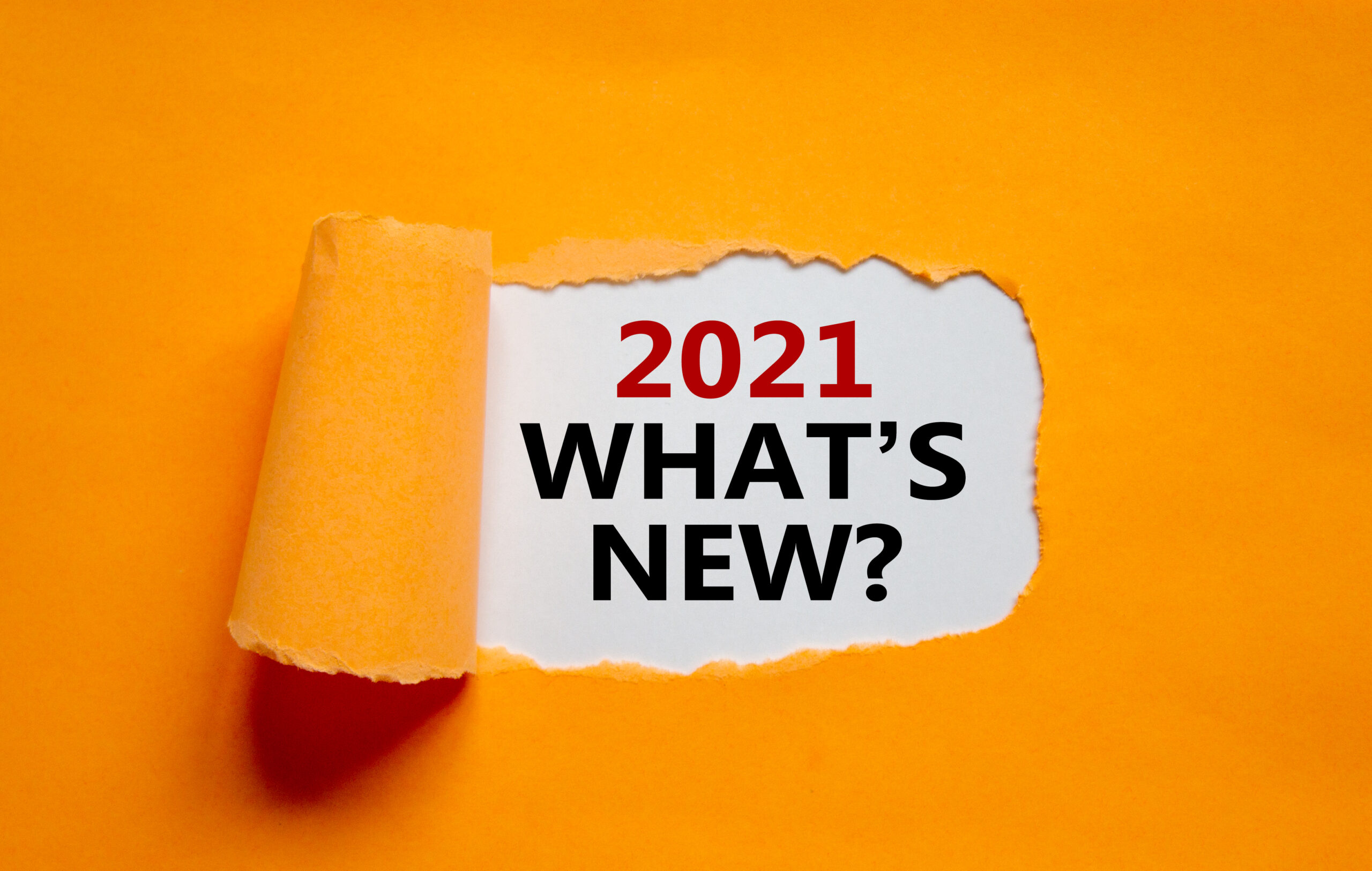2021 what is new symbol. The words '2021 what is new' appearing behind torn orange paper. Business and 2021 what is new concept. Copy space.