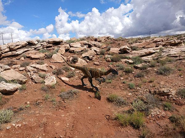 A dinosaur replica in the grass